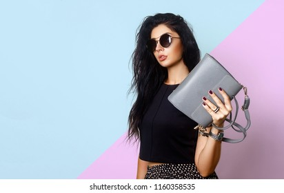 Portrait of a beautiful girl posing in studio in black blouse, skirt and fashion sunglasses, holding handbag near the face. The concept of stylish and sexy women, perfect skin and body