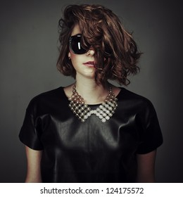 portrait of a beautiful girl posing in a studio in a leather dress and sunglasses