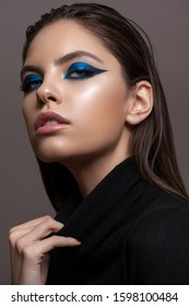 Portrait of a beautiful girl with professional makeup, ideal skin, bright blue graphic smokey eyes and in black sweater