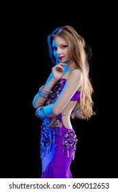 Portrait of a beautiful girl in a purple oriental dancer suit posing on a black background in a scenic blue light