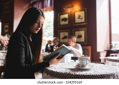 Portrait of a beautiful girl reading book in cafe