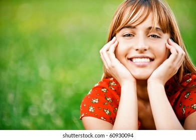 Portrait of beautiful girl in red dress which sits on green grass.
