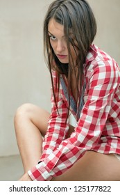 portrait of a beautiful girl in a red shirt in a cage