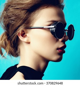 Portrait of a beautiful girl in round glasses on a blue background in the studio, the concept of beauty