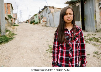 Portrait of beautiful girl in shanty town. Poor infant concept