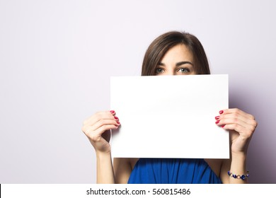 Portrait of a beautiful girl with a sheet of paper in his hands