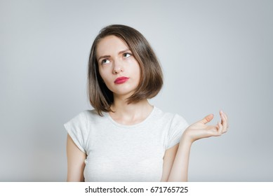 Portrait of a beautiful girl showing indifference, isolated on a gray background