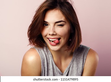 Portrait of beautiful girl showing tongue and winking over pink background.