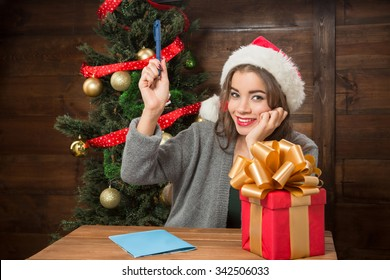 Portrait of beautiful girl sitting at the wooden table and thinking about interesting New Year and Christmas congratulations to write in postcard.