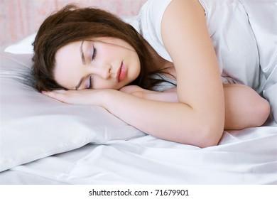 portrait of beautiful girl sleeping in bedroom on linen