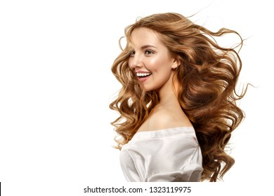 Portrait of beautiful girl with smiley face. Model laughing looking at camera. Flying curly hair. Happy womans smile, clean skin, natural make-up, and white teeth. White background.