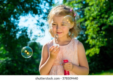 portrait of a beautiful girl with soap bubbles