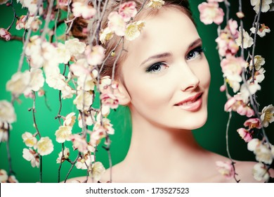 Portrait of a beautiful girl standing among the branches of cherry blossoms. Spring.