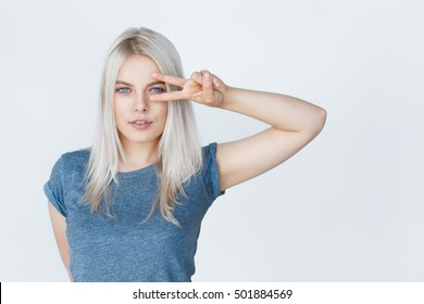 portrait of a beautiful girl student with blond hair wearing clean t-shirt showing peace gesture isolated on grey background. Amazing blue eyes and grey dyed hair.