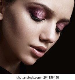 Portrait of a beautiful girl in the studio with pink make-up, face close up