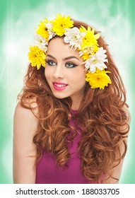 Portrait of beautiful girl in studio with yellow and white chrysanthemums in her hair. Sexy young woman with blue eyes and bright flowers. Creative hairstyle and makeup, fashion photo studio shot