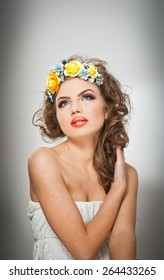 Portrait of beautiful girl in studio with yellow roses in her hair and naked shoulders. Sexy young woman with professional makeup and bright flowers. Creative hairstyle and makeup, studio shot