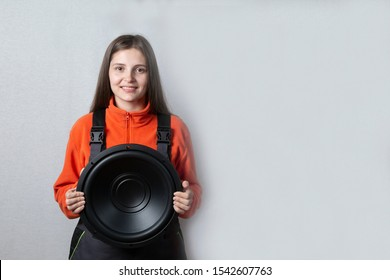 Portrait of a beautiful girl with a subwoofer. Car audio system.