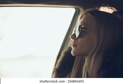 portrait of beautiful girl in sunglasses in the car