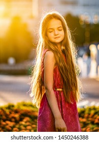 Portrait of a beautiful girl at sunset, a child in the sun, the sun in the girl's hair, child portrait close-up