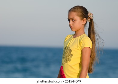 portrait of a beautiful girl at sunset. girl in yellow t-shirt on sky background