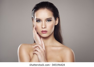 Portrait of a beautiful girl touching her face