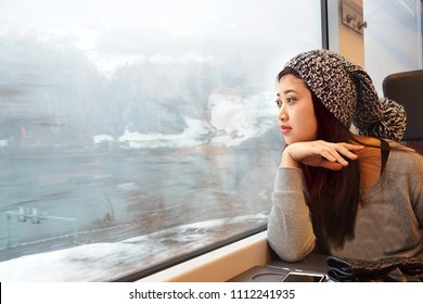 Portrait of beautiful girl traveling by train and looking out to the window with lake and snow background in winter.Enjoying travel.Business,Vacation,Holiday,Transportation Concept.