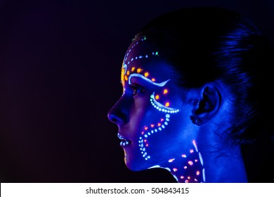 Portrait of beautiful girl with ultraviolet paint on her face. Girl with neon make-up in color light.