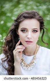 Portrait of a beautiful girl in vintage summer dress on a lawn in the grass, closeup, professional makeup