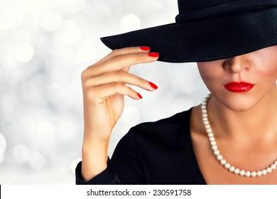 Portrait of a beautiful girl wearing black hat.