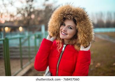 Portrait of beautiful girl wearing winter fur jacket with hoodie.