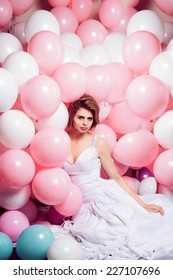 Portrait of beautiful girl in white bride dress with white and pink balloons