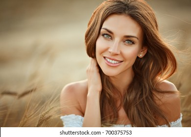 Portrait of a beautiful girl in a white dress in a field with ears at sunset in summer. Close-up