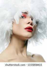 Portrait of Beautiful Girl in white feathers. young sexy woman with red lips, feather hat, closeup. Beauty make-up