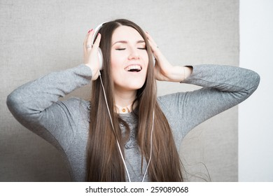 Portrait of a beautiful girl who is listening to music in her headphones