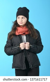 Portrait beautiful girl in winter black jacket and hat, on blue background