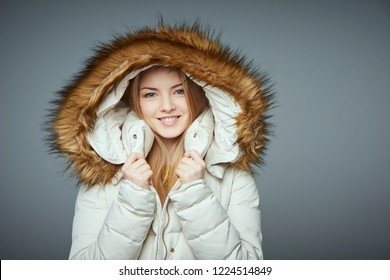 Portrait of beautiful girl in winter coat smiling looking at camera on grey studio background