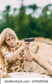 Portrait of a beautiful girl in yellow camouflage and a cap with a gun in her hands