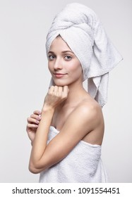Portrait of beautiful girl. Young woman with bath towel on the head. Female covered in bath towel posing on gray background.