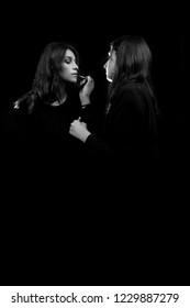 portrait of beautiful girls, in black and white, the makeup artist passes the lipstic to the sensual girl posing on the black background