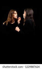 portrait of beautiful girls, the makeup artist passes the lipstic to the sensual girl posing on the black background