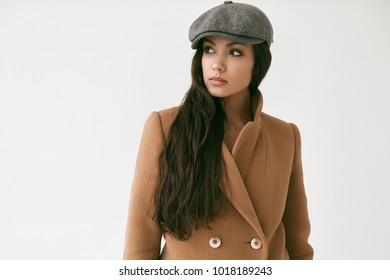 Portrait of beautiful glamor brunette woman wearing coat isolated on white background in studio