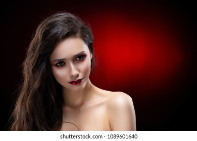 Portrait of a beautiful glamorous brunette girl with naked shoulders. Shimmering makeup, red lips. Healthy smooth skin. Black and red background. Copy space. Commercial and advertising design.