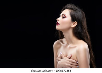 Portrait of a beautiful glamorous brunette girl sensually covers her naked breast with her hands. Shimmering makeup, red lips. Healthy smooth skin. Isolated on black. Copy space.
