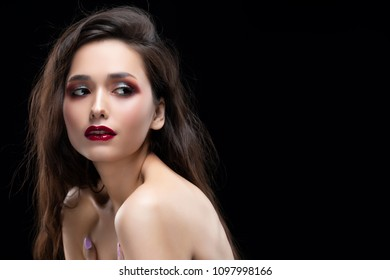 Portrait of a beautiful glamorous brunette girl with naked shoulders. Shimmering makeup, red lips. Healthy smooth skin. Isolated on black. Copy space. Commercial and advertising design.