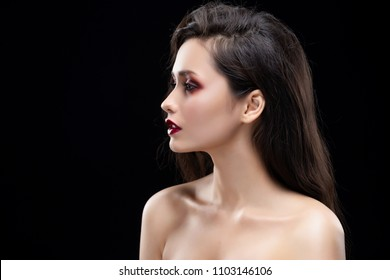 Portrait of a beautiful glamorous brunette girl sideways. Shimmering makeup, red lips. Healthy smooth skin. Isolated on black. Copy space. Commercial and advertisement design