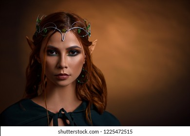 Portrait of beautiful gorgeous princess of elves in silver tiara with emeralds looking at camera. Charming and elegant girl with red hair and make up wearing dark green cloak tied around neck.