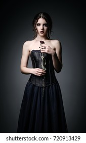 Portrait of beautiful goth girl holding a withered rose in hands