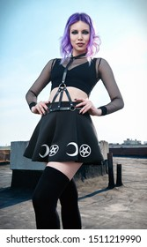 Portrait of beautiful gothic girl on the housetop. Pastel goth with violet (purple) hair in black clothes