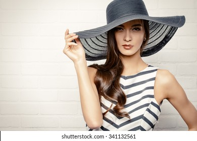 3f16f11806f Portrait of a beautiful graceful woman in elegant hat with a wide brim.  Beauty